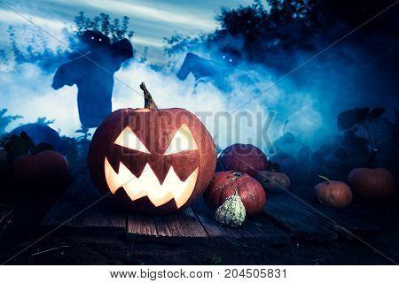 Glowing Halloween Pumpkin On Dark Field With Scarecrows