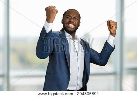 Businessman with clenched fists and teeth. Young manager clenching teeth and raised fists. Concept of great businessman achievement and victory.