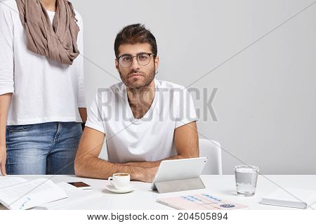 Confident Young Bsinessman With Earring And Stubble Studying Documents At Office With Mug Of Coffee,