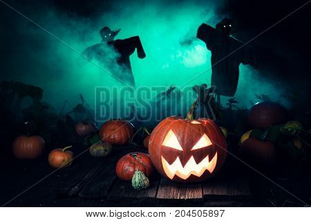 Scary Pumpkin With Green Mist And Scarecrows For Halloween