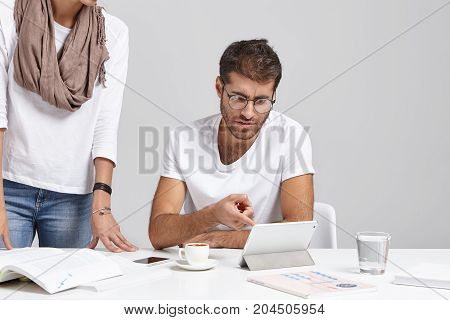 Young Caucasian Bearded Boss In Glasses And T-shirt Sitting At White Office With Diagram And Tablet
