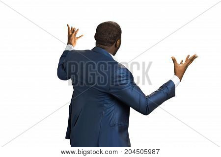 Back view of shocked and scared young businessman. Rear view of businessman holding arms out wide and arguing. Holds hands upwards.