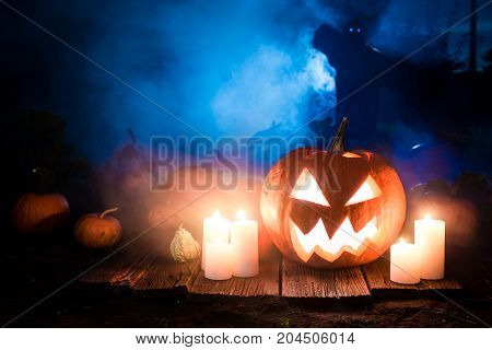 Glowing Halloween Pumpkin With Scarecrows On The Field