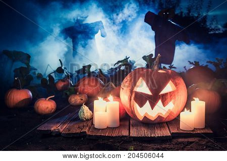Glowing Pumpkin With Blue Mist And Scarecrows For Halloween