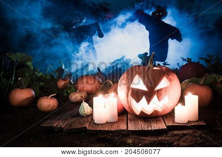 Glowing Pumpkin With Scarecrows On The Field For Halloween