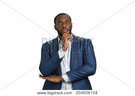 Thoughtful businessman on white background. Young entrepreneur  thinking about business holding hand under chin.