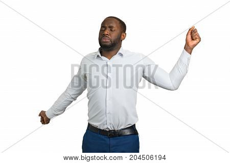 Stretching businessman with closed eyes. Young man stretched out his arms wide on white background. Afro american manager starts his day with morning exercises.