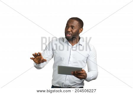 Successful businessman speaking and gesturing. Bearded entrepreneur using computer tablet and speaking with colleagues.