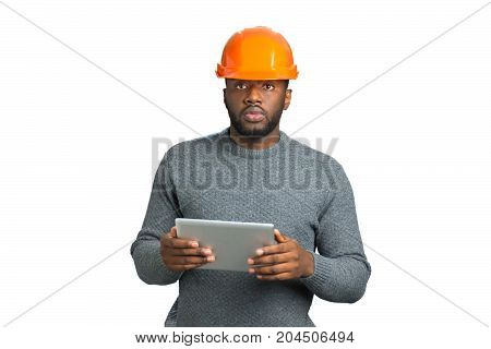 Confident architect in safety helmet. Afro american foreman in orange helmet and computer tablet on white background.