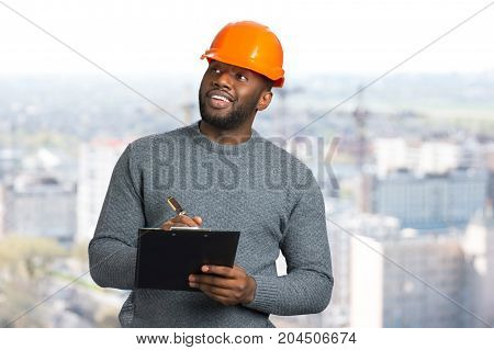 Smiling architect writing on clipboard. Manual worker in casual wear and helmet holding pen and clipboard. Cheerful foreman on blurred background.