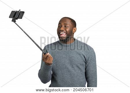Happy young man taking selfie. Cheerful afro american guy taking picture with monopod on white background.