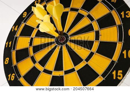 Three Yellow Darts In Bullseye On Dartboard