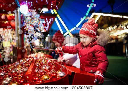Kids At Christmas Fair. Children Shopping Xmas Gifts.