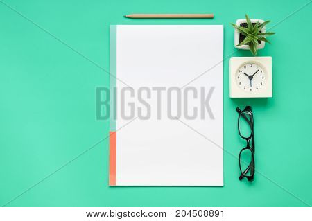 Top view of office desk - paper pencil eyeglasses clock on modern fresh green table