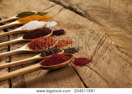 Variety Of Spices In Wooden Spoons On Wooden Rustic Kitchen Table