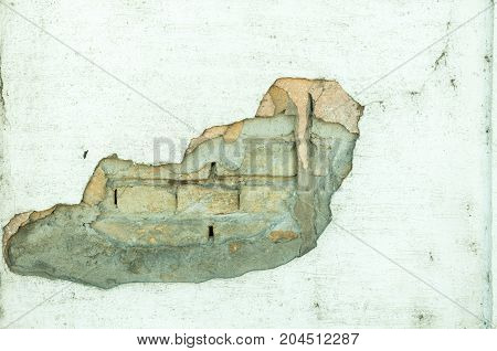 Damaged wall of house with hole in the plaster and brick background