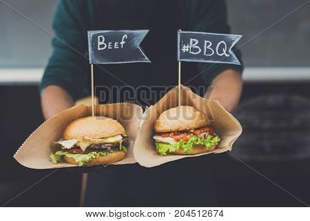Street fast food festival, hamburgers cooked at barbecue outdoors. Cookout american bbq food, closeup in chef's hands in craft paper, copy space