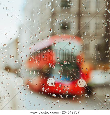 Raindrop On Glass And Red London Bus Lights Background.