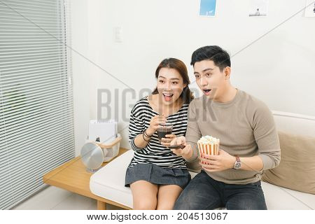 Relaxed Young Couple Watching Television In Their Living Room