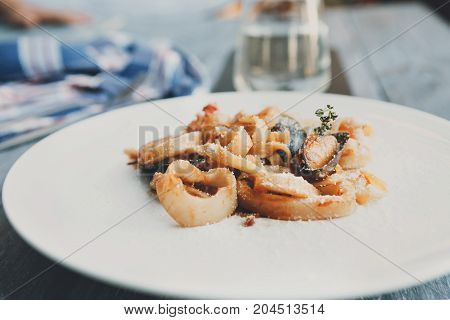 Restaurant food. Traditional italian seafood tomato pasta with calamari rings and mussels on white round plate. Diet and healthy meals, selective focus, closeup