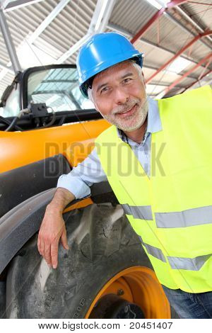 Site manager standing by machine