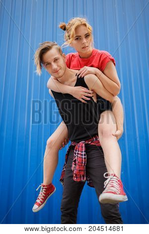 Girl on the back of her boyfriend. Young modern stylish hipsters couple on blue background, sunny portrait couple teenagers.