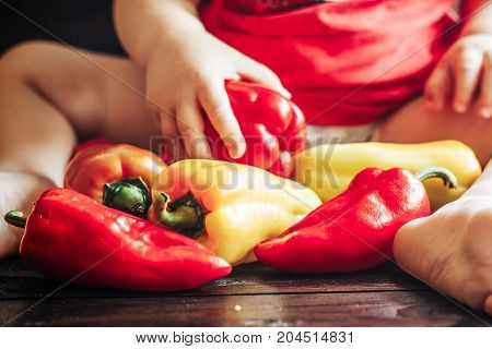 Baby Sitting On Table And Playing With Sweet Bell Peppers. Healthy Food For Children