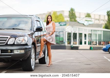 Attractive young woman standing in a car park, choose a car to buy. Used car theme