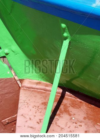 rudder and hull of a green and blue wooden fishing boat in a harbor in close up