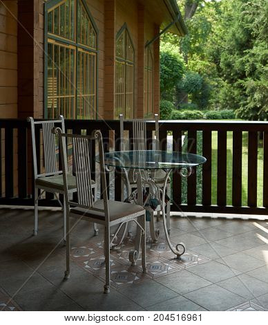 Summer terrace with table and chairs. Summer wooden cafe on terrace with vintage furniture on background forest landscape. Tables and chairs in cafe on veranda overlooking forest