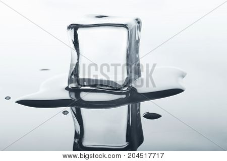 Melting ice cube with reflection on white background. Closeup of cold crystal blocks cutout