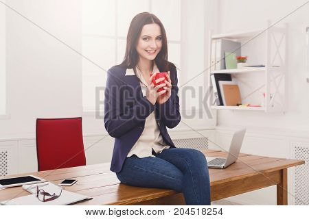 Coffee break. Pensive businesswoman relaxing, sitting at workplace on office desk with cup of drink