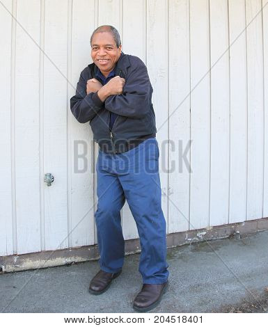 African american male senior expressions against a wall outdoors.