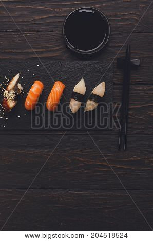 Colorful sushi platter in japanese restaurant, with chopsticks and soy sauce on dark wooden background, vertical, top view, flat lay