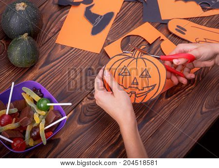 Cloud frame with ghost, pumpkins, spiders and bats cut out of paper. Background of brown wooden boards.