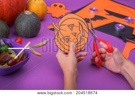 Cloud frame with ghost, pumpkins, spiders and bats cut out of paper. Purple background.