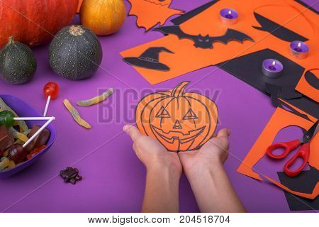 Cloud frame with ghost, candies, pumpkins, spiders and bats cut out of paper. Isolated on purple background.