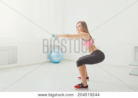 Deep squat. Side view of young beautiful woman in sportswear doing squat exercises and holding at gym.