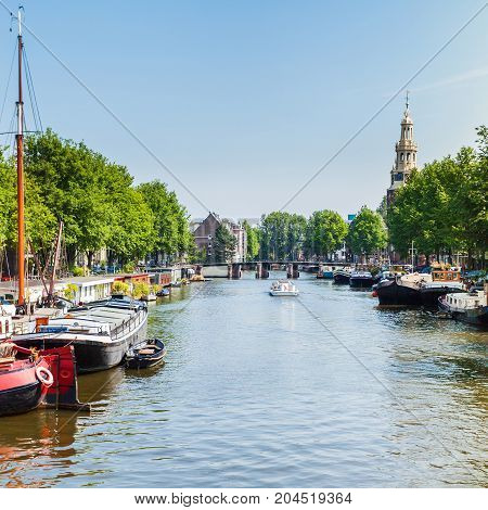 Typical street in Amsterdam with canal, colorful houses and water boat house in the Dutch style. Netherlands.