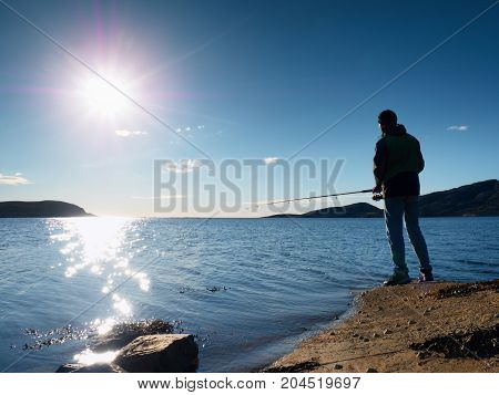 Fisherman Check Fishing Line And Pushing Bait On The Rod, Prepare Himself And Throw Lure Far Into Pe