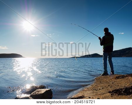 The Active Man Is Fishing On Sea From The Rocky Coast. Fisherman Check Pushing Bait