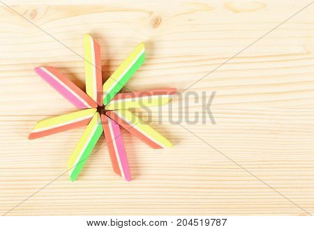 New bright erasers over wooden background with empty space for your text