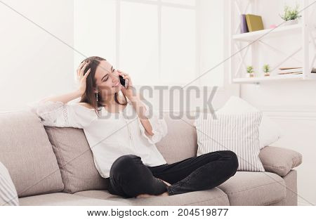 Happy woman talking on mobile phone sitting on comfortable couch at home, copy space