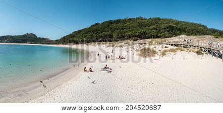 ISLAS CIES SPAIN - CIRCA SEPTEMBER 2017: Unidentified people relax on the sand beach of Playa de Rodas on the Cies Islands of Spain included in the Atlantic Islands of Galicia National Park.