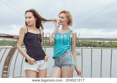Women flirt with each other outdoors. They are in love with each other.