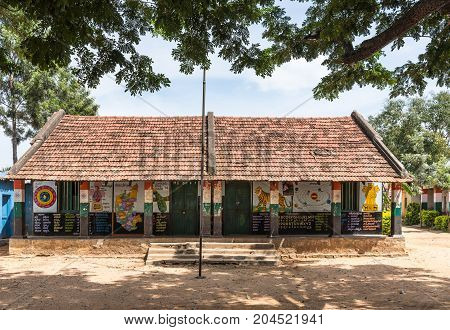 Mysore India - October 27 2013: Government higher primary school building under red tiled roof and with walls painted with colorful images and texts of basic knowledge. Under bluish sky and green trees