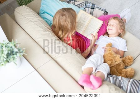 High angle view of pretty little girl taking nap while her blond-haired elder sister reading adventure story aloud, interior of cozy living room on background