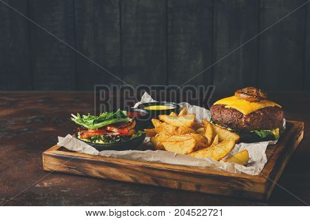 Take away burger menu on wooden tray. Black bun cheeseburger with baked potato wedges and sauces set, fast food concept