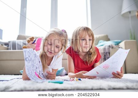 Cute little sisters painting coloring book with felt-tip pens while lying on cozy carpet at spacious living room