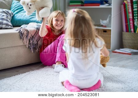 Cheerful little sisters gathered together at cozy living room and playing with teddy bears